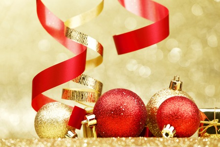 Colorful decorative curling ribbons and balls over glitter background photo