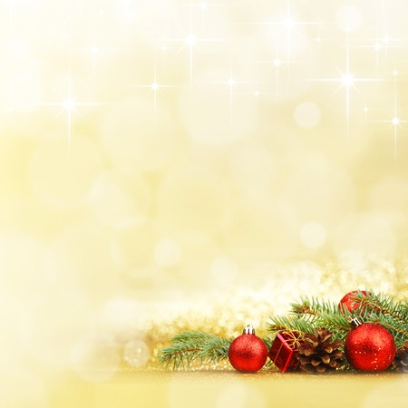 Christmas card with fir tree branch and decoration on golden glitter background 写真素材