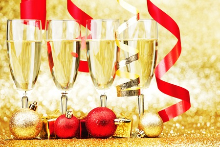 Glasses of champagne and red ribbons on golden background photo