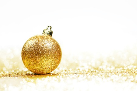 gold ornaments: Beautiful Glitter christmas ball close-up on shining background with white copy space