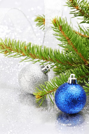 Christmas fir tree branch and decoration on silver glitter background photo