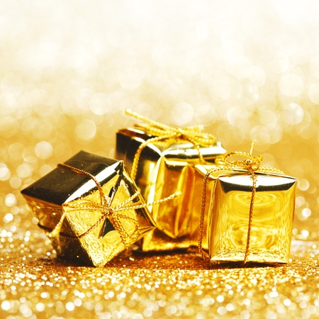 Decorative golden boxes with holiday gifts on shiny glitter background photo