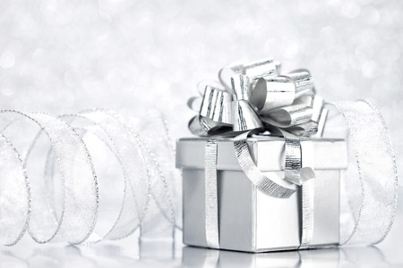 Decorative silver box with holiday gift on shiny glitter background photo