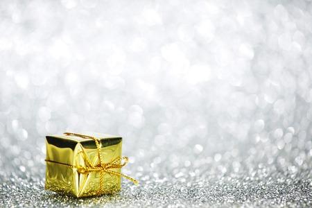 Beautiful golden small holiday gift box on silver glitters photo