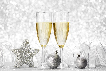 Glasses of champagne and christmas decoration on silver background photo