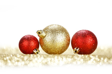 Three chritmas balls on glitters isolated on white background photo