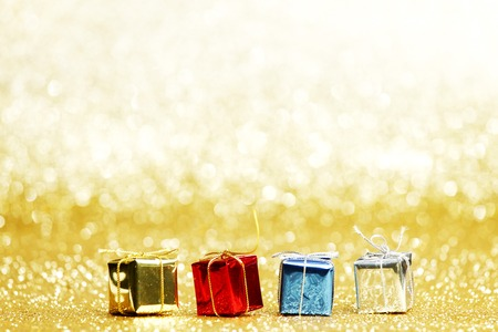 Small decorative colorful presents on glitter background photo