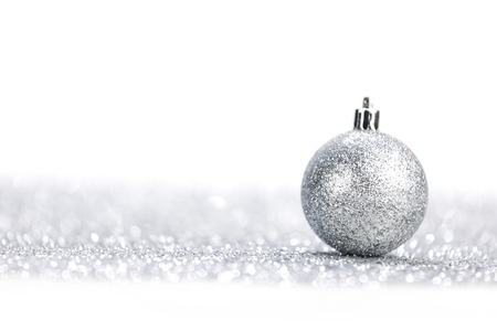 One chritmas ball on glitters isolated on white background photo
