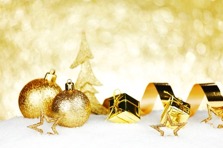 Golden Christmas decorations on snow close-up photo