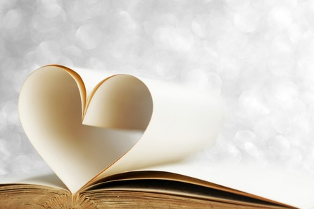 Heart shaped book pages on glitter background photo