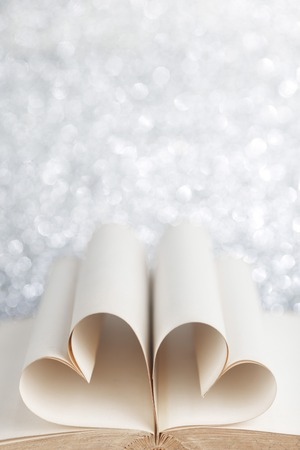 Pages of open book rolled in heart shape on glitter background photo