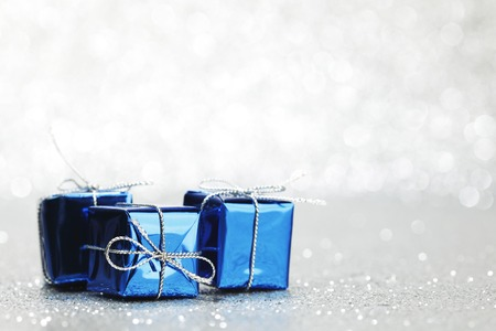 Small boxes with decorative holiday gifts on silver bokeh background photo