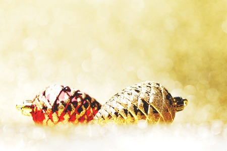Decorative christmas pine cones on golen glitter shiny background photo