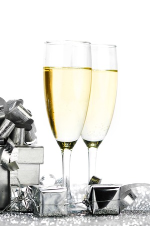 Glasses of champagne and christmas gifts on silver background photo