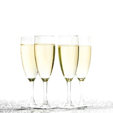 Glasses of champagne on glitters isolated on white background photo