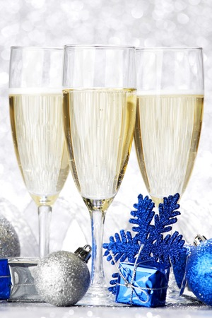 Glasses of champagne and decorative christmas balls on glitter background photo