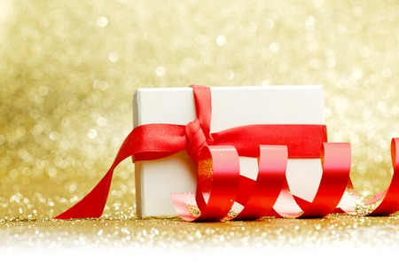 Decorated present in white box with red ribbon on golden background photo