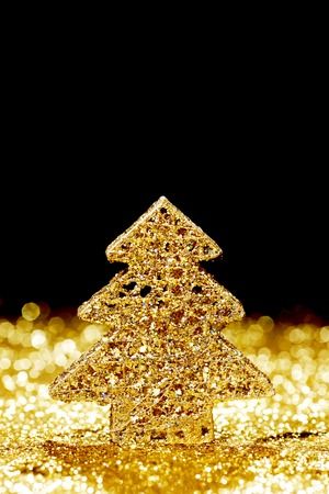 Beautiful golden decorative christmas tree on golden glitter background with black copy space photo