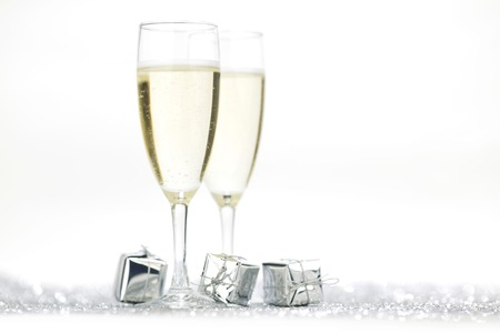 Two elegant flutes of sparkling champagne with decorative silver gifts photo