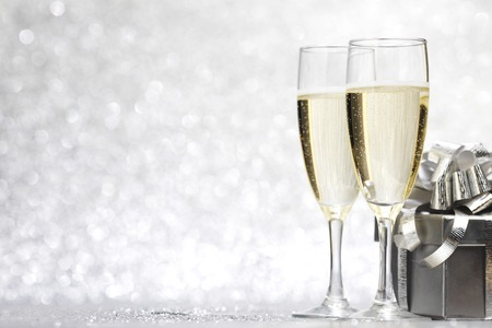 Champagne and present on silver bokeh background Фото со стока