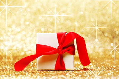 White gift box with red ribbon bow on golden glitter background photo