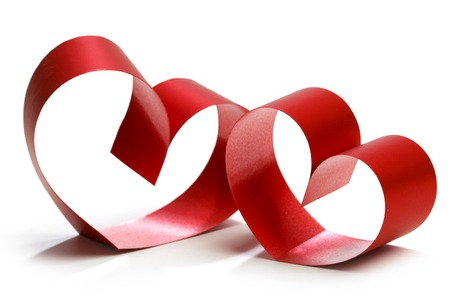 Two linked hearts of red ribbon isolated on white background photo
