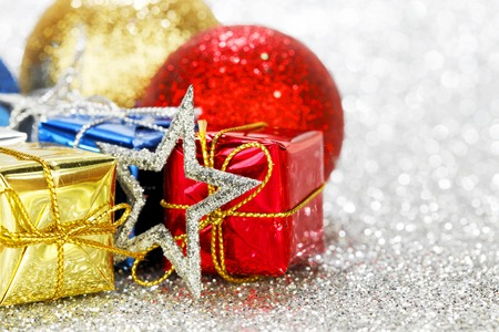 New Year gift and balls on shiny silver bokeh background photo