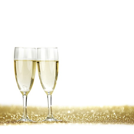 Two champagne glasses and golden shiny glitters isolated on white background photo