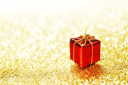 Red decorative box with holiday gift on gold glitters background photo