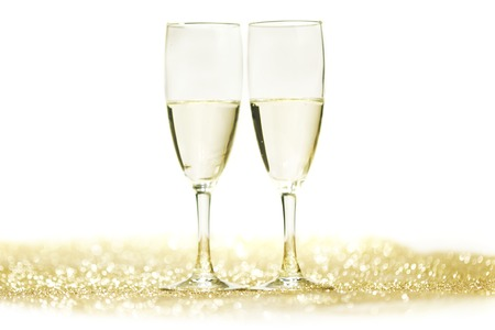 Champagne glasses on glitters isolated on white background photo
