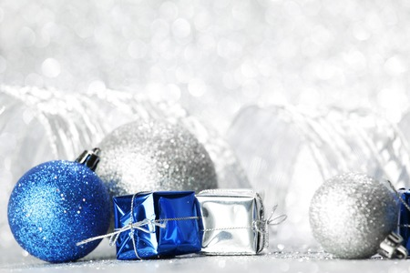 Decorative Christmas balls and gifts on silver bokeh background photo