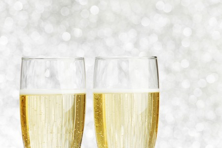 Pair of champagne flutes on shiny glitter background photo