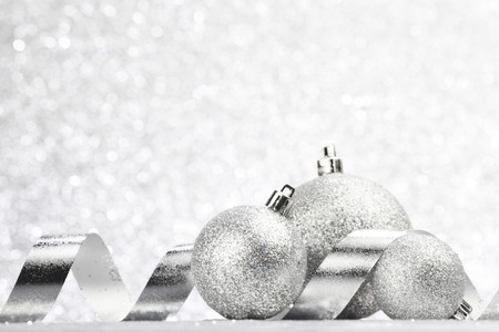 silver balls: Christmas decorative balls and ribbons on light silver bokeh background