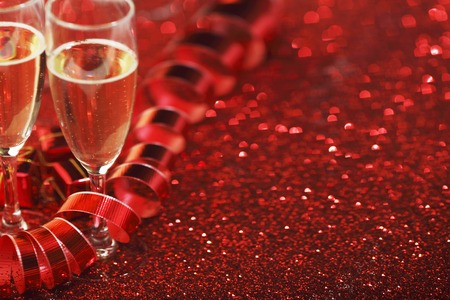 Glasses with Champagne and gifts on red glitters background photo