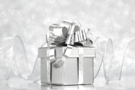 Gift box with tied to bow satin ribbon over bokeh background photo