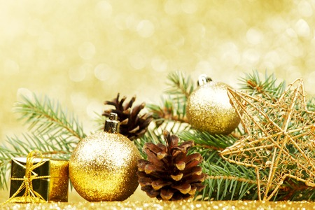 Christmas card with fir tree branch and decoration on golden glitter background photo