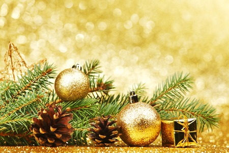 Christmas card with fir branch and decorations on golden gitter background photo