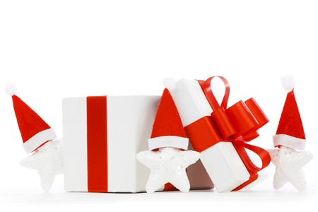 White gift box with red ribbon, stars with santa claus hats isolated on white background photo