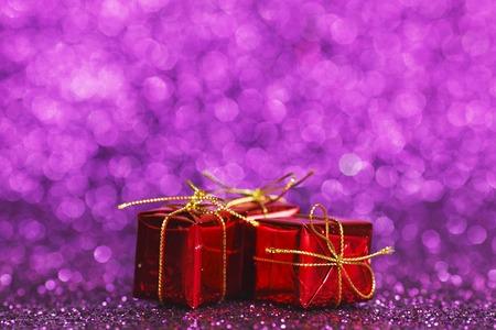 Small decorative gift boxes on shiny glitter background photo