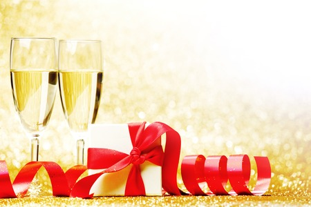 Glasses of champagne and box with gift on golden background photo