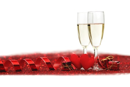 Glasses with Champagne and handmade hearts on red glitters isolated on white background photo