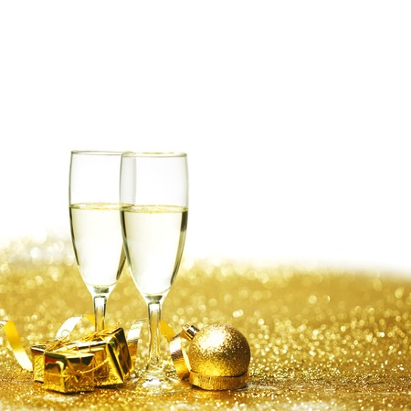 Champagne in glasses and gift box on golden background photo