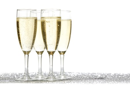 Four champagne glasses and silver shiny glitters isolated on white background photo