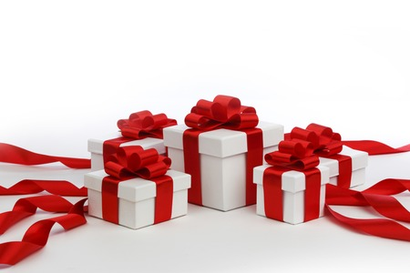 Holiday presents wrapped in white paper with red ribbons, isolated on white photo