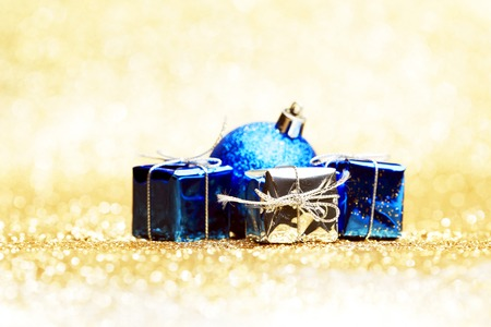 Christmas ball and gifts on abstract glitter background photo