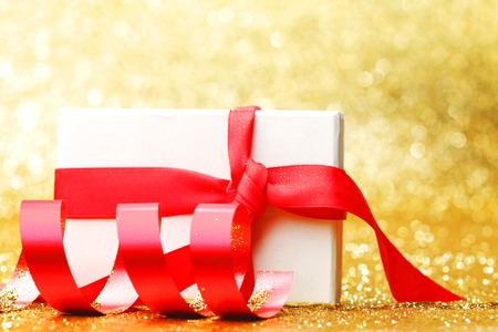 White gift box with red ribbon on golden glitter background photo