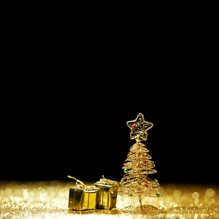 Decorative golden toy christmas tree and gifts on black background photo