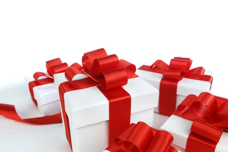 Boxes with presents wrapped in white paper with red ribbons, isolated on white photo