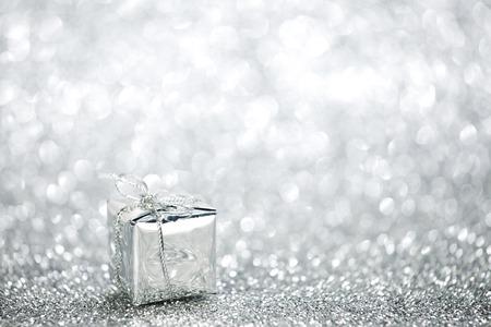 Beautiful small holiday gift box on silver glitters photo