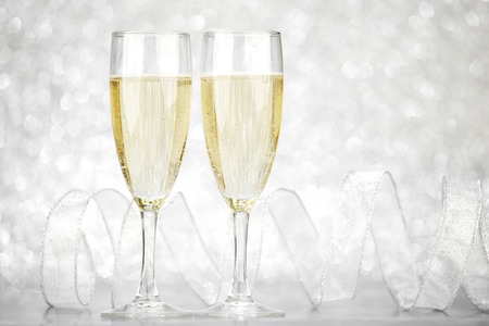 Two champagne glasses and ribbon on silver bokeh background photo